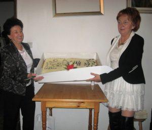 Elżbieta Tylkowska z lewej i Alicja Bednarek z prawej prezentują jubileuszowy tort