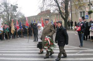 Składanie wiązanek kwiatów pod tablicą Józefa Piłsudskiego. Na pierwszym planie kombatanci