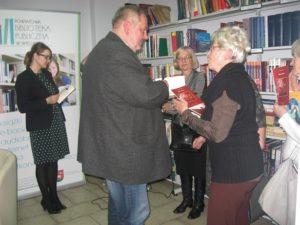 """Ksiądz Zbigniew Bigaj podpisuje tomik""""Mojej Mamie"""""""
